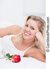 Young woman with a rose smiling
