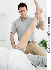 Physiotherapist raising the leg of a patient in a room