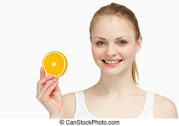 Cheerful woman presenting an orange slice against white...
