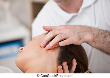 Doctor manipulating the side of the head of his patient in a...