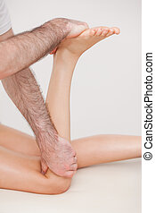 Podiatrist manipulating the leg of his patient while holding his foot and his knee indoors