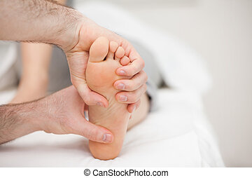 Two hands holding a foot in a room