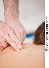 Doctor using his finger to massaged the back of his patient...