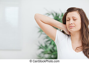 Woman placing her hand on her painful neck in a room