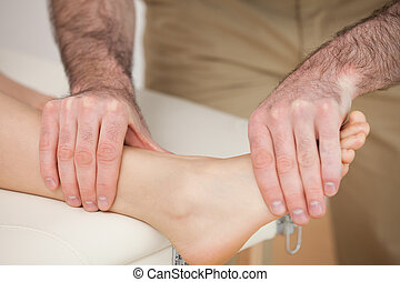 Man massaging the foot of a woman in a room