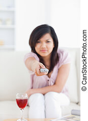 Blurred woman holding a television remote
