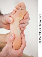Physiotherapist working on a barefoot in a room