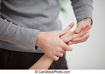 Masseur massaging the hand of  a woman