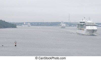 Cruise liners go between little rock islands on bay, time lapse