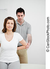 Serious osteopath holding the elbow of a patient in his...