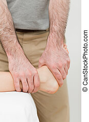 Osteopath manipulating the ankle of a patient