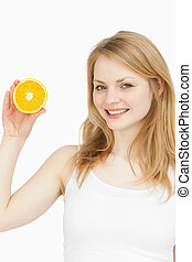 Smiling woman presenting an orange against white background