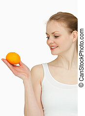 Smiling woman presenting a tangerine while looking at it...