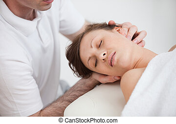 Woman being massaging by the doctor while having the head...