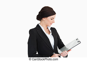 Woman in suit looking at a clipboard