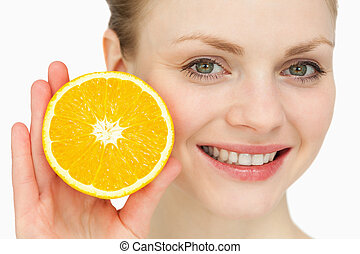 Blond-haired woman presenting an orange against white...