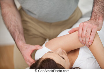 Osteopath making a joint mobilization in his medical office