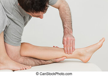 Serious osteopath massaging the shin bone of a patient in a...