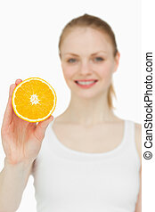 Blonde-haired woman holding an orange against white...