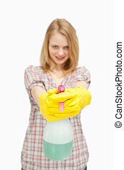 fair-haired woman holding a spray bottle