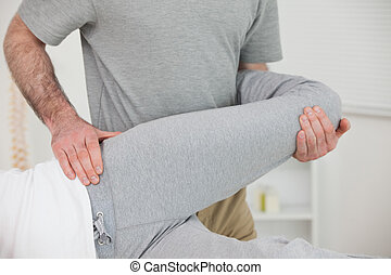 Chiropractor stretching the leg of a patient in a room