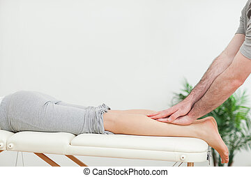 Close up of a masseur massaging the calves of a woman