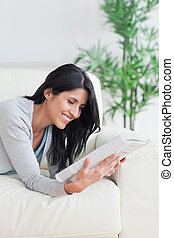 Woman smiling while she reads a magazine