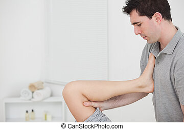 Chiropractor raising the leg of his patient against his...