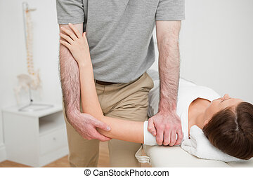 Physiotherapist pressing the shoulder of a woman in a...