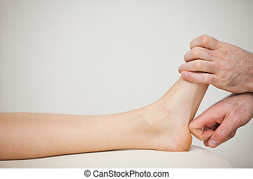 Physiotherapist using his forefinger to massage a foot in a...