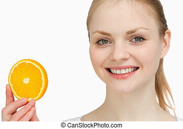 Smiling woman presenting an orange slice against white...