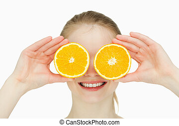 Close up of a smiling woman placing oranges on her eyes...