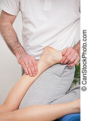 Podiatrist manipulating the ankle of his patient while putting his foot on him indoors