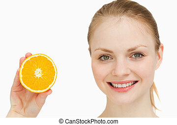 Close up of a cheerful woman presenting an orange against...