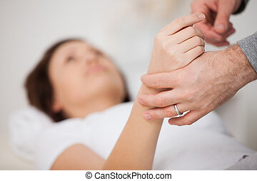 Hand of a woman being manipulated in a medical office