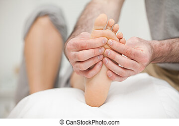 Sole of a foot being touched by a doctor in a room