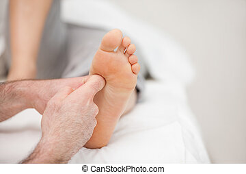 The side of a foot being massaged in a room