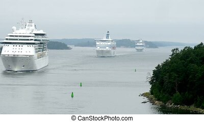 Cruise liners manoeuvring between rock islands in mist, time lapse