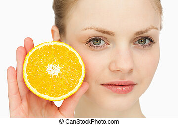 Close up of a woman presenting an orange against white...