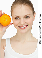 Smiling blonde-haired presenting an orange against white...