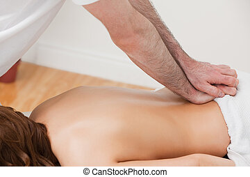 Therapist massaging the back of his patient while standing...