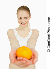 Smiling woman presenting a tangerine against white...
