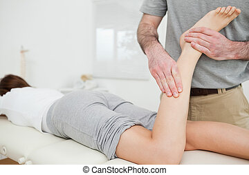 Woman lying while a doctor is examining her leg