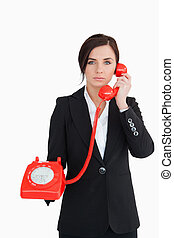 Business woman using a red dial telephone against white...