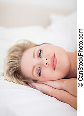 Young woman smiling while she is drowsy on her bed