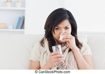 Sick woman blowing her nose while holding a glass of water