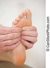 Barefoot being massaged by a physiotherapist in a room