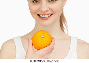Close up of a woman holding an orange while smiling against...