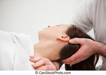Doctor manipulating the neck of a woman in a room