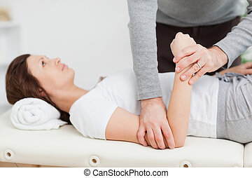 Physiotherapist manipulating the arm of a peaceful woman in...